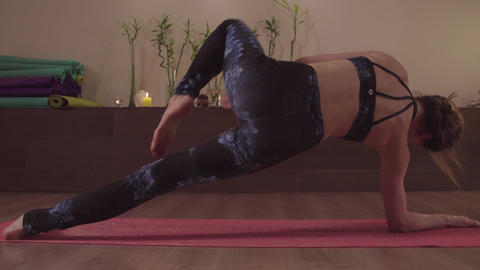 Young flexible woman practicing yoga indoors Footage