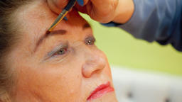 Face elderly woman while eyebrows makeup in beauty studio close up Footage