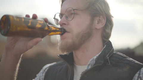 Bearded man with glasses drinking beer and enjoying beverage outdoors. Guy Live Action