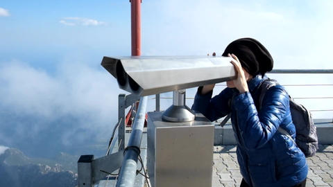 Young woman looking through telescope at viewpoint in the mountains Live Action
