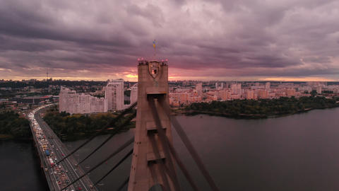 Auto bridge with triangular ropes over the Dnipro river in summer at sunset Footage