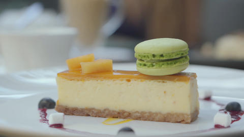 Beautifully served tasty cheesecake with mango and berries and green macaron in Footage