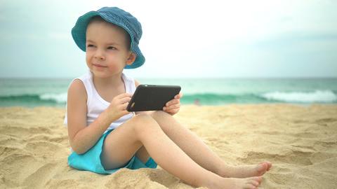 Cute boy sitting at sandy beach and using smartphone app Archivo