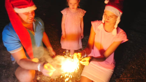 Happy family with child in Christmas hats burning Bengal lights in hands Footage