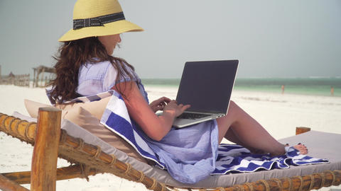 Young woman uses laptop on white beach near ocean Archivo