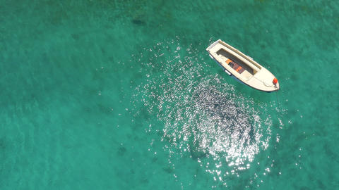 Aerial - Boat Floating On Clear Turquoise Water With Beautiful Sun Reflection stock footage