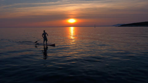 Aerial - Man SUP boarding for recreational persuit at sunset Footage