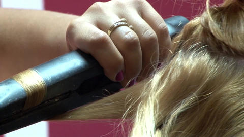 Hair stylist passing the hair his client through a hot plate to spread it 03 Footage