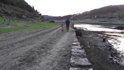 Father who was walking with his son on the bank of a river then descends into hi Footage
