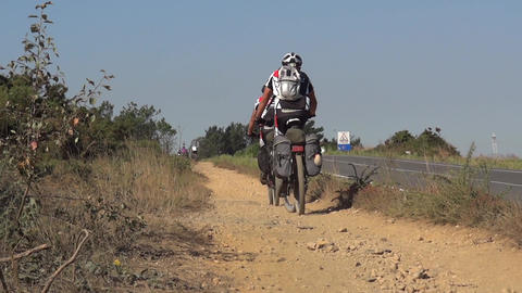 Cyclists who pedal on a dirt road located next to a paved road that rarely pass Footage