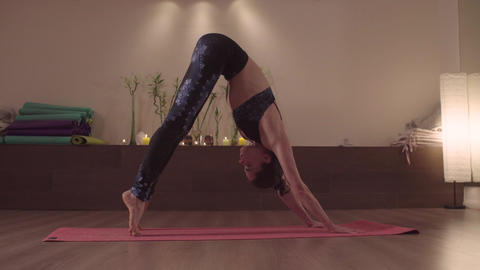 Attractive woman doing yoga exercises in nice studio Footage