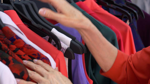 Hands of elderly woman choosing clothes in fashion shop while shopping Footage