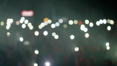 Crowd waving flashlights during a music event Live Action