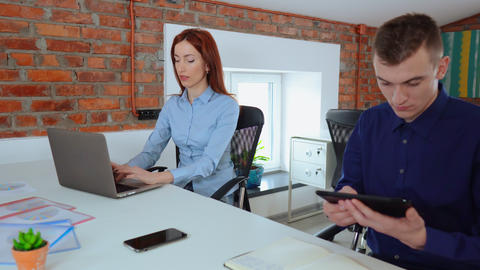 Female and male accountants sitting at the desk, working on a desktop computer Live Action
