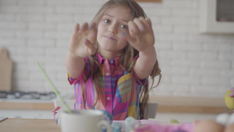 Cute emotional little girl with long hair showing to camera hands in the blue Footage