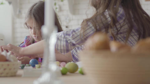 Woman and little girl coloring easter eggs with colors and brush. Preparation Live Action