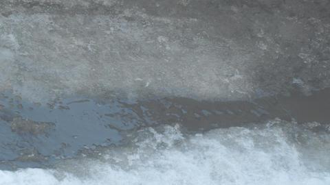 Spring stream flows through the asphalt Footage