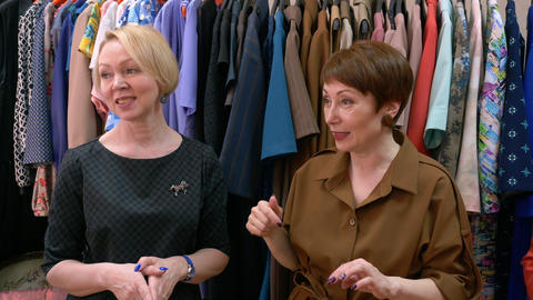 Two middle age women designers talk about fashion trends on the background of Live Action