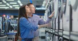 Young man and woman in appliances store choose to buy washing machine for home Footage