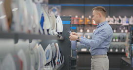 A young handsome man chooses an iron in a consumer electronics store for his new Footage