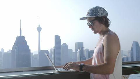 Freelancer using laptop on modern city background during summer vacation Footage