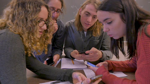 Three young college university students and a teacher all look at the same mobile phone in a science Footage