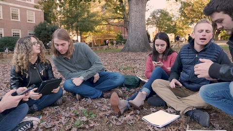 Group of male and female college students all using their mobile devices, digital tablets, and smart Footage