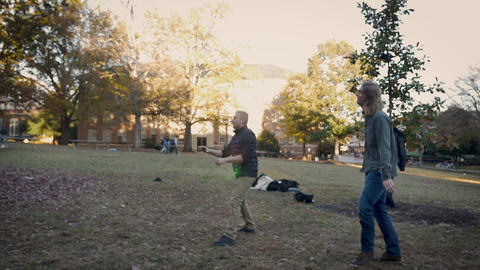 Two male college students playing frisbee at a university campus in slow motion Live Action