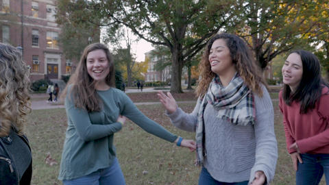Diverse group of four excited happy college women laughing and celebrating on a university campus in Footage