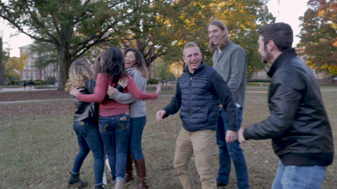 Happy diverse group of college students hugging, laughing and having fun on a university campus in Live Action
