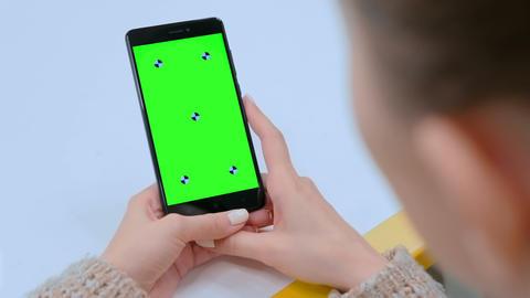 Woman touching blank green screen of black smartphone - swipe hand gesture Footage