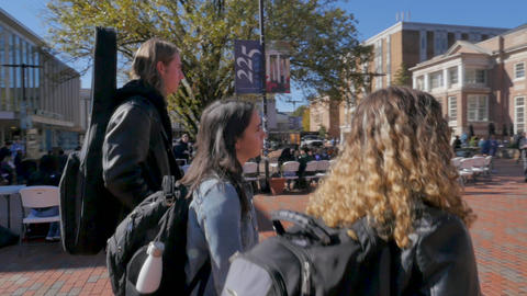 Two female college students and a young male university student walking through a busy campus and Live Action