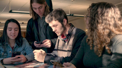 Two men and two women college students laughing and using their mobile phones in a cafeteria in slow Live Action