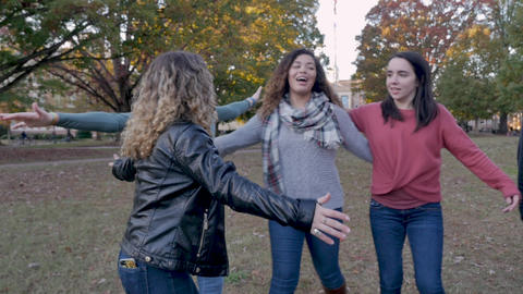 Diverse group of four college women give each other a group hug celebrating and cheering outside on Live Action
