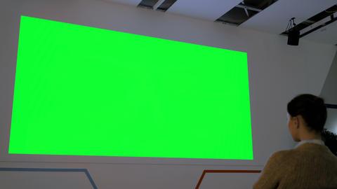 Woman looking at large blank green screen - cinema mock up Footage
