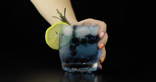 Woman hand takes and put refreshing soda lemonade blue cocktails with lemon Live Action
