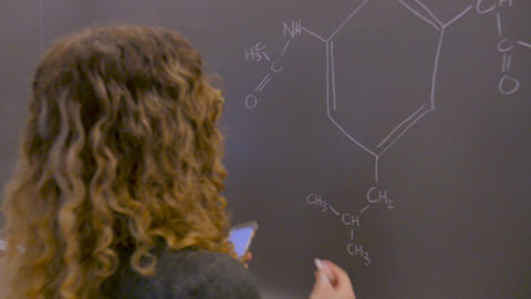 Young college or high school student using a smart phone mobile app to solve a chemistry problem on Live Action