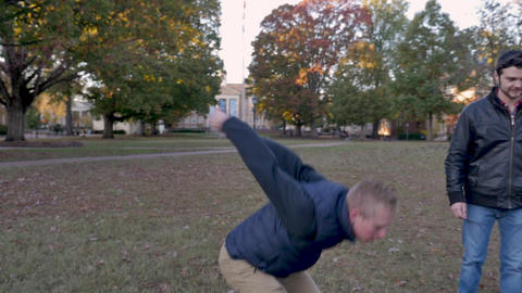 Young man slipping in wet grass after doing a flip-flop gymnastics move on a college campus in slow Footage