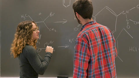 Female student helping a male college student solve a chemistry problem on a chalkboard in slow Live Action