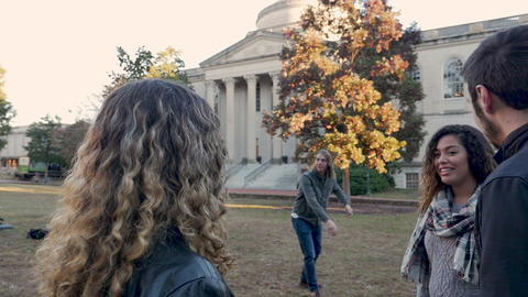 Diverse group of friends talking while someone is playing frisbee on a college campus in slow motion Live Action