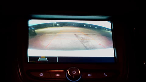 Car Rear View Camera While Vehicle Reversing at Night. Using the Backup Camera During the Evening Footage