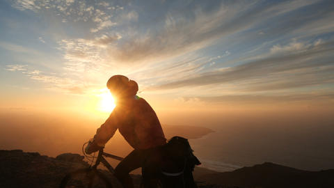 Man rides a bicycle high in mountains near cliff edge above the ocean against Footage