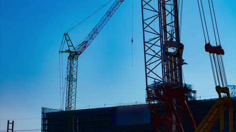 A time lapse of moving cranes behind the blue sky at the under construction dusk Archivo