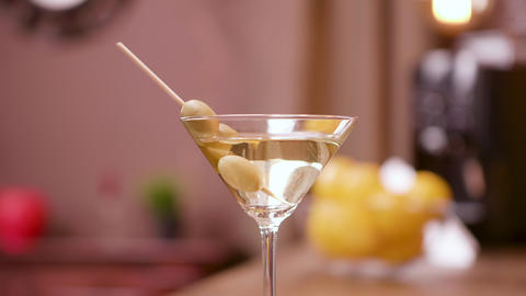 Close up parallax shot of a martini glass garnished with olives Footage