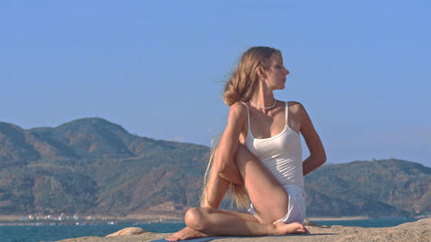 Blond Girl in Top Sits on Rock in Yoga Pose Hands behind Back Footage