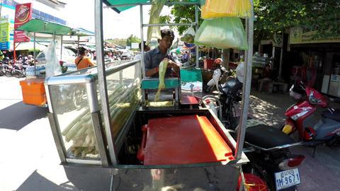 Vendor with a portable sugar cane juicer fresh raw sugar cane drinks Footage