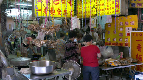 Vendor selling zongzi dumplings and customers at traditional market Live Action