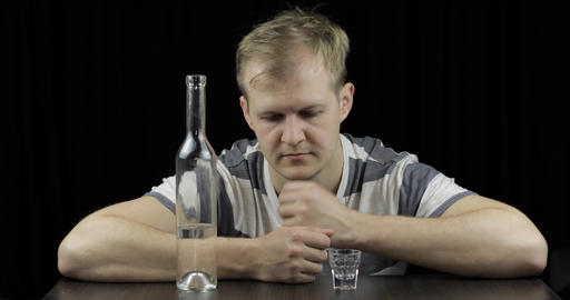 Depressed man drinking vodka alone in a dark room. Concept of alcoholism Footage