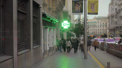Street with walking people and pharmacy sign in Madrid, Spain Footage