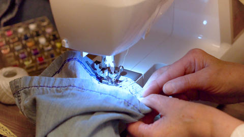 Sewing denim jeans. Repair jeans by sewing machine. Slow motion clip Live Action